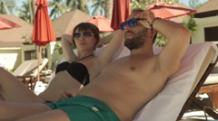 Couple relaxing and talking while lying on sunbed - stock footage