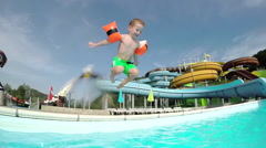 SLOW MOTION: Happy kid smiling and jumping into pool water Stock Footage