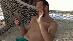 Man on hammock chatting on tablet computer lying on hammock on exotic beach, 240 Stock Footage