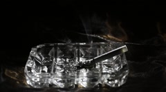 Cigarette in an ashtray on a black background. Ashtray with cigarette rotates - stock footage