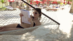 Young woman reading newspaper while lying on hammock, on the beach, 240fps Stock Footage