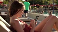 Woman using smartphone during sunbath Stock Footage