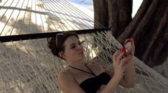 Young, happy woman watching movie on smartphone lying on hammock on the beach, Stock Footage
