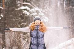 Winter fun. Girl in winter clothes throwing snow up in air cheerfully. Stock Photos