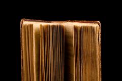 Ancient book shot on black background Stock Photos