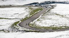 Stock Photo of Cyclist goes downhill along a mountain road in a snowy landscape