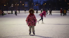 The girl is standing on the outdoor ice rink Stock Footage