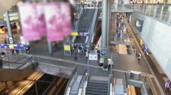 Busy railway station hall, crowd walking the stairs, trains arriving on platform Arkistovideo