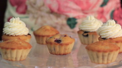Whipped cream frosting applied to berry cupcakes Stock Footage