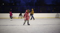 Girl learning to skate and falls on the ice - stock footage