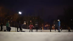 People skate on the outdoor ice rink - stock footage