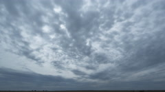 Gray clouds hurrying overhead, hiding the sun over a prairie landscape, time Stock Footage