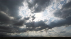 Sunbeams falling through ragged gray clouds onto a prairie landscape - stock footage