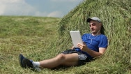 Stock Video Footage of Man in dark blue t-shirt lies on a haystack and communicates via tablet computer