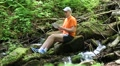 Man sits near small river in the forest and communicates via tablet computer Footage