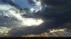 Sun rays beneath departing storm clouds at sunset, time lapse Arkistovideo