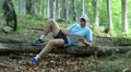 Man with tablet PC lies on a log in forest Footage