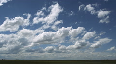 Puffs of cumulus drawing together over green prairie, time lapse Stock Footage