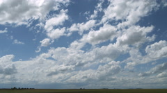 Cumulus clouds and distant storm with anvil top over prairie landscape Stock Footage