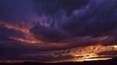 Dramatic dark purple and gold clouds at sunset, time lapse Stock Footage