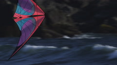 Tracking a colorful kite flying above waves below coastal cliffs Stock Footage