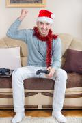 Stock Photo of young man playing video games with wireless Bluetooth joystick