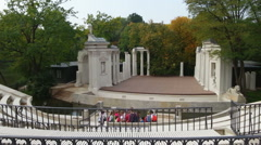 Old amphitheater in Lazienki Park, Warsaw. Group of tourists sitting on benches Stock Footage