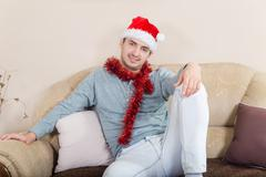 Stock Photo of The young man ornate with Christmas decorations and red hat