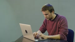 Man is Looking at the Screen Attentively Typing Puts a Glasses on Approaches to - stock footage