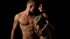 Guy with a beautiful figure hugs a girl with a rope instead of clothes Stock Footage