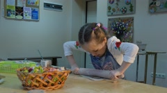 Kid is Rolling a Piece of Clay With Roller Trying Hard Basket is on a Table - stock footage