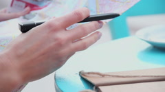 Closeup of female hands holding map, writing notes, checking route during trip Stock Footage