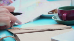 Close-up of woman's hand with pen writing notes, tourist in cafe checking map Stock Footage