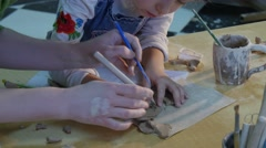 Teacher Helps the Kid to Cut Out a Clay Figurine With Spatula Knife Shows and - stock footage