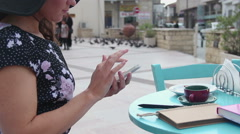 Female sitting at street cafe table, using smartphone, typing message, scrolling Stock Footage