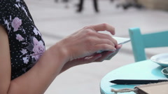 Woman at outdoor cafe using mobile app on smartphone, texting, sending e-mail Stock Footage