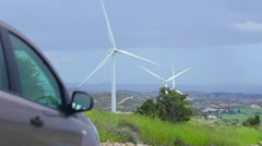Car standing near wind farm, alternative power sources, fuel cost, energy crisis Stock Footage