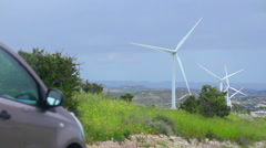 Car near spinning wind turbines, renewable energy source, alternative to fuel Stock Footage
