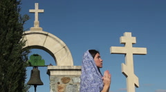 Young woman praying to God with clasped hands, stone cross, religious symbol - stock footage