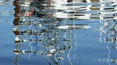 Abstract reflections of boats and masts on rippling harbor water - stock footage