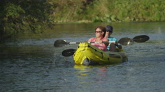 SLOW MOTION: Happy smiling couple in boat oaring on river Stock Footage