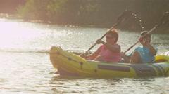 SLOW MOTION: Happy smiling couple enjoying summer sunset canoeing - stock footage