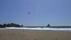 A colorful kite swooping close past the camera on an Oregon beach Stock Footage