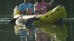 SLOW MOTION CLOSE UP: Happy couple kayaking on calm water - stock footage