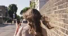 Beautiful woman using smart phone technology app walking through city Stock Footage