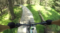 FPV: Extreme downhill biker riding on wooden bike trail track Stock Footage