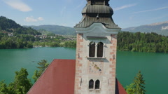 AERIAL CLOSEUP: Flying around lake Bled church tower - stock footage