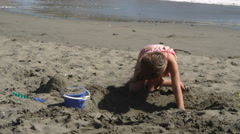A little girl digging in the sand on a beach with surf in background Stock Footage