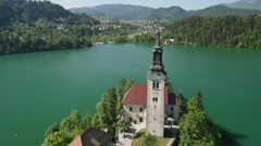 AERIAL: Beautiful small church on island Bled in natural lake - stock footage