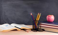 Stock Photo of Desktop in classroom ready to learn from textbooks
